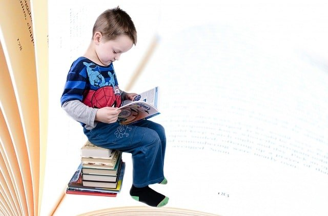 boy reading on stack of books