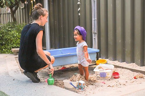 infant playing in sand pit and providing childcare tauranga