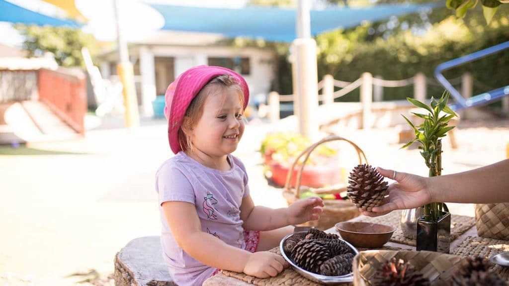 child being offered a pine cone childcare philosophy